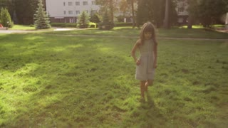 little girl running on the grass in the Park under the water spray