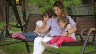 mother reading a book to children sitting in the Park