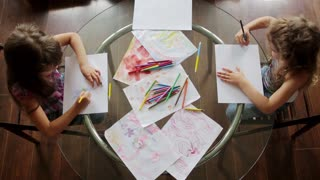 two little girls draw with crayons sitting at table. top view