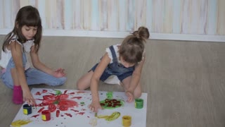 two little girls draw with finger paints