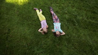 two little girls lying on the grass and talk. girlfriend spend time together. top view