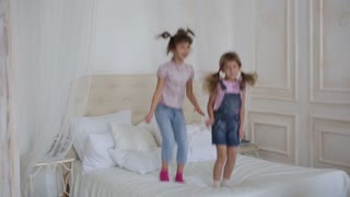 two little girls playing and jumping on the bed