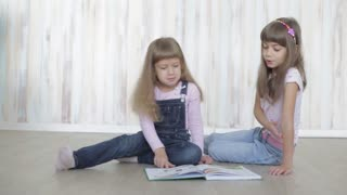 two little girls reading a book lying on the floor