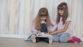 two little girls reading a book sitting on floor