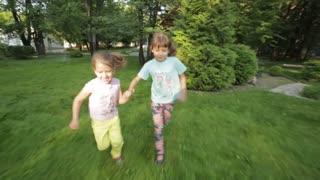 two little girls run through the grass holding hands. children spend time outdoors