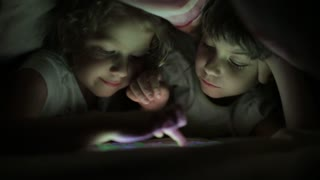 two little girls sisters playing on a tablet PC hiding under a blanket