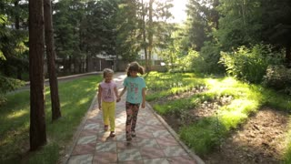 two little girls walk through the Park and holding hands. children spend time outdoors