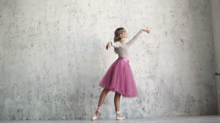 a ballet dancer in pointe shoes and a classic tutu gracefully raises her leg.