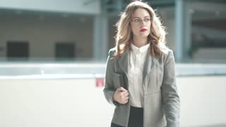 a business woman in a gray jacket goes to the lobby of the business center. girl in a business suit in the workplace. slow motion