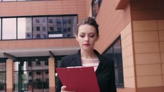 A business woman quickly walks with a confident gait. A folder for papers in the hands. The girl is late for a business meeting