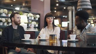 a company of three friends in a restaurant and a cafe. two young men and a girl are sitting at a table in a cozy restaurant.
