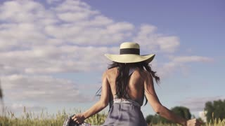 a cute and carefree girl runs across the field and throws up her straw hat. Portrait of a happy young woman. Back view. slow motion