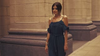 A girl is walking around the city on a summer night.
