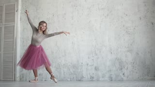 A graceful ballerina dances in a pink tutu and pointe shoes. graceful, light movements. slow motion