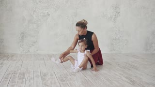 A little ballerina is studying ballet with her teacher. The choreographer and her little student