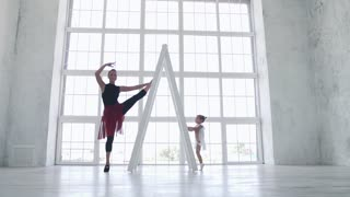 a little funny girl tries to repeat the movements behind the ballerina in the ballet class. slow motion