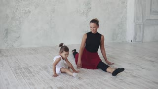 a small ballerina in a ballet class. teacher and little girl are sitting on a string