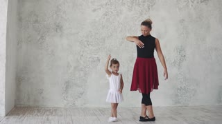 a small ballerina repeats the movements behind the teacher. ballet lesson in the studio