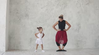 A small ballerina repeats the movements of the teacher and jumps. ballet lesson in the studio