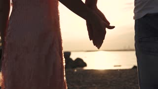 A touch of male and female hands against the sunset. Love, romance, relationships