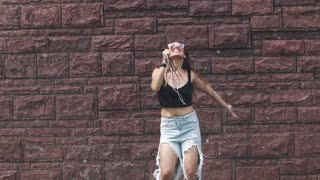 A wet girl sings songs in a mobile phone instead of a microphone and dances crazy under the spray of water on the street. slow motion