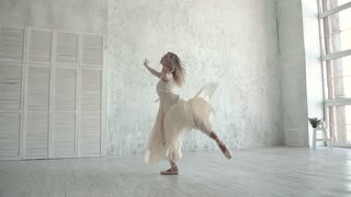 A young ballerina is dancing in a white light dress. ballet dancer in pointe shoes. concept of lightness and grace. slow motion