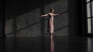 a young beautiful ballerina in pointe shoes and a long fluttering dress elegantly moves and dances. slow motion