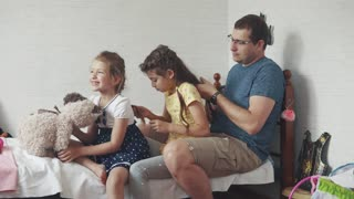 a young father braids his daughter's pigtails. family portrait. older sister braids pigtails younger sister