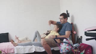 A young father spends time with his little daughter. Father and child sit on the bed at home and play. Parent-child friendship