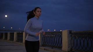 a young girl in sports clothes Jogging on the waterfront in the moonlight. the athlete is engaged in sports on the background of the lights of the city at night. slow motion