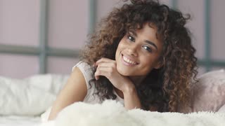 a young girl just wake up and basked in bed. smiling attractive hispanic woman lying on bedsheet and smiling