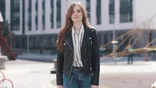 A young girl walks around the city and on the move takes off her jacket. portrait of a beautiful young woman against a background of modern architecture. slow motion