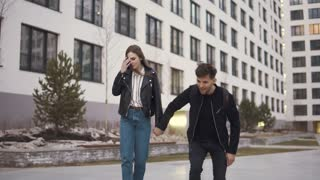 a young man and his girlfriend ride skateboards around the city. a couple of lovers are actively spending time together