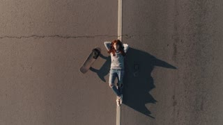 aerial. A teenager with a skateboard and lies on the roadway and listens to music on headphones. young girl hippy. View from above