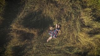 aerial. a young woman in a bright dress lying in the hayloft. The concept of unity with nature and tranquility. view from above.