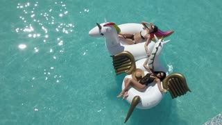 Aerial - best girlfriends on vacation on a hot sunny day. Sexy girls in bathing suits sunbathe and relax lying on inflatable mattresses in the pool. Shooting with quadrocopter