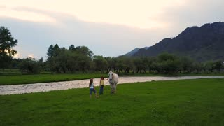 Aerial. children on a meadow at the foot of the mountains play with the wild horse. two little girls sisters in the village. Aerial camera shot