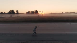 aerial. girl is riding on a skateboard along an empty highway at sunset.