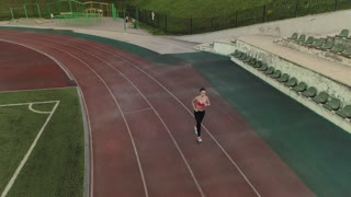 aerial. girl jogging in the stadium in the evening.