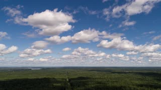 Aerial Hyperlapse of sky. Timelapse clouds over forest.