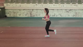aerial. jogging. sports girl running through the stadium. young woman jogging outdoors
