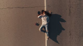 aerial. portrait of a hipster girl lying on a skateboard on the roadway. View from above