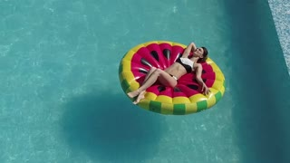 Aerial - sexy girl in swimsuit, sunbathing on an inflatable mattress in the shape of a watermelon. brunette sun tanning in the pool. Shooting with quadrocopter