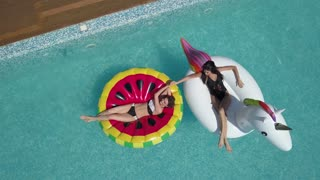 Aerial - Young beautiful girlfriends are sunbathing in the pool lying on inflatable mattresses. Attractive young girls rest on a sunny day. Shooting with quadrocopter