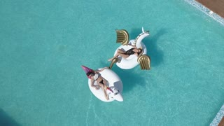 Aerial - young women sunbathing on air mattresses the unicorn and the Pegasus. Attractive young girls rest on a sunny day in pool. Shooting with quadrocopter
