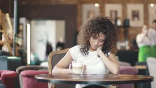 an attractive hispanic girl texting in a mobile application on a smartphone sitting in a cafe