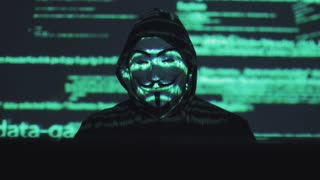 anonymous in the mask steals user data on the network. hacker against the background of running code