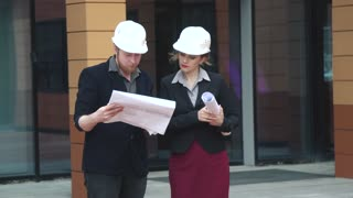 architects holding a building plan at the construction site and discuss the construction of the building. young woman and man builders. businesswoman at work