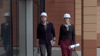 architects inspecting construction site. a young woman and her colleague are on the background of a modern building. engineer are working in helmets. SLOW MOTION
