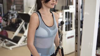 athlete doing exercises on the triceps on the machine in the gym. girl in sportswear on training